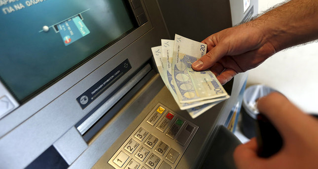A man withdraws sixty Euros, the maximum amount allowed after the imposed capital controls in Greek banks, at a National Bank of Greece ATM in Piraeus port near Athens, Greece June 30, 2015 (Reuters Photo)