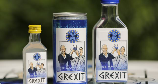 """Samples of sour schnapps, an energy drink and a vodka called """"Grexit"""" with caricatures of Greek PM Tsipras (R) and Minister of Finance Varoufakis (L) raising their glasses under a miserable looking Angela Merkel"""