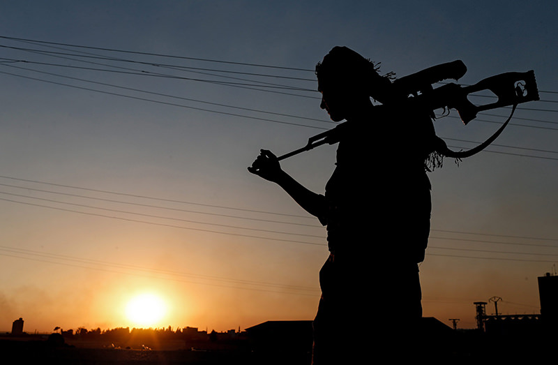 A member of Kurdish People Defence Units (YPG) guards during a sunset near Tel Abyad border gate, northern Syria, 23 June 2015 (EPA Photo)