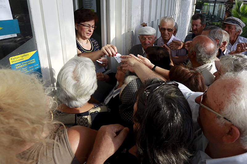 Pensioners scuffle to get priority tickets from a bank staff member as they wait to collect part of their pensions on the Greek island of Santorini, Greece (Reuters Photo)