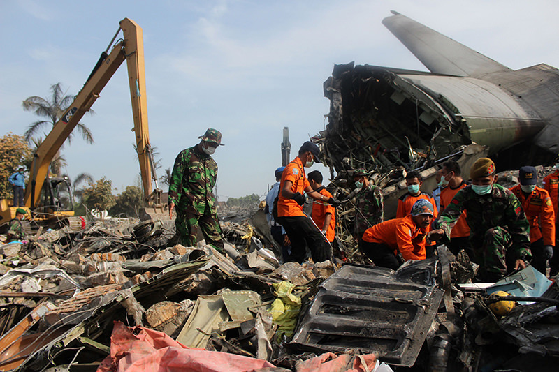 Soldiers search the tail wreckage at the crash site of an Indonesian Air Force C-130 Hercules aircraft a day after the accident, next to a destroyed commercial building in Medan (AFP Photo)