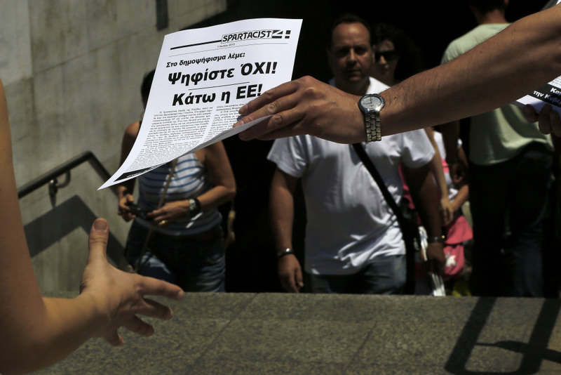 A man passes out a leaflet reading in Greek ,Vote NO in the referendum, Down with the EU, to a passerby outside of the Metro station in Syntagma Square in central Athens on Thursday.