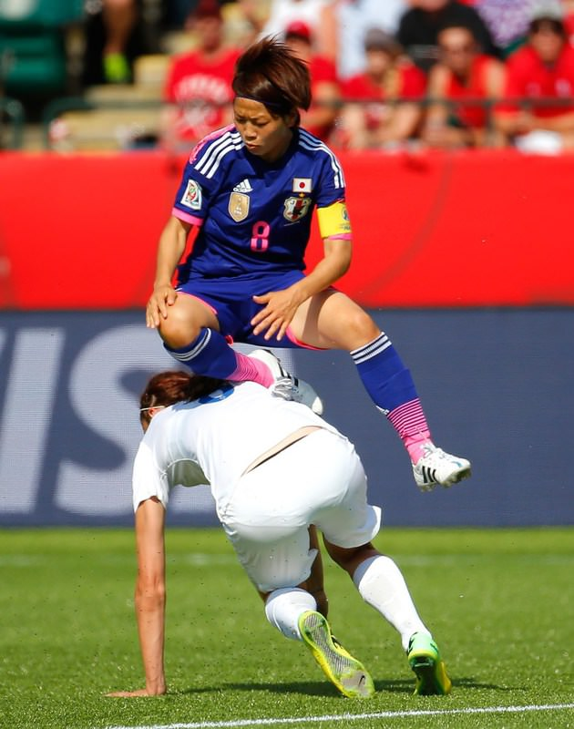 Aya Miyama of Japan leaps over Jill Scott of England during the 2015 FIFA Women's World Cup Canada 2015 Semi Final match between Japan and England at Commonwealth Stadium.