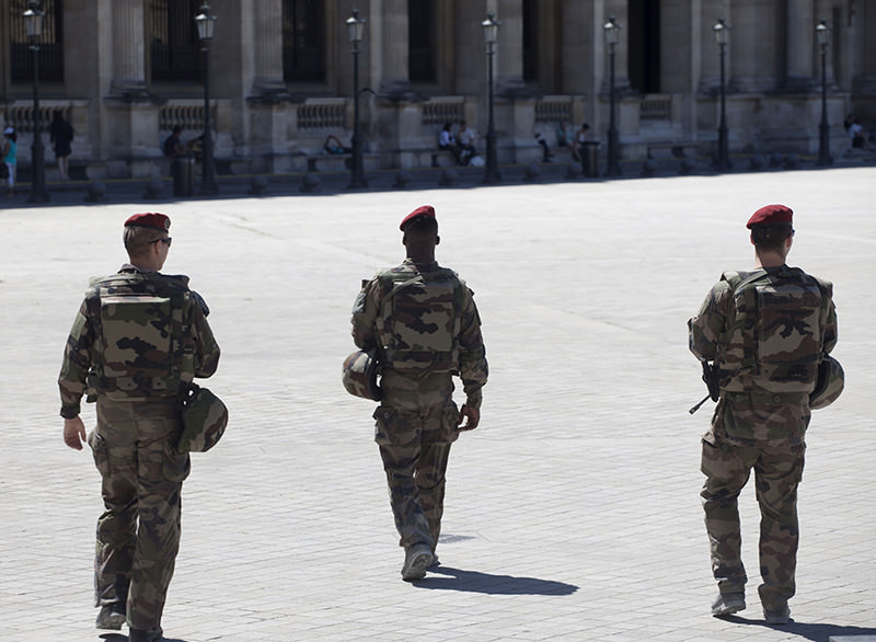 French soldiers, on patrol as part of the national security alert system, walk across the courtyard of the Louvre in Paris on June 30, 2015 (AFP Photo)
