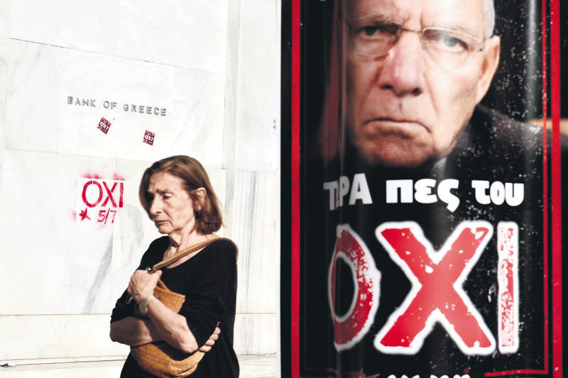 A woman passes by the headquarters of the Bank of Greece daubed with the word ,NO, and a poster with a portrait of German Minister of Finance Wolfgang Schaeuble that reads ,Now tell him NO,, ahead of a referendum in Athens.