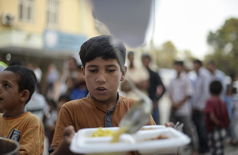 A young Syrian refugee lines up for food as Syrians break their fasting on June 20, 2015 in Aku00e7akale, in Turkeyu2019s u015eanlu0131urfa province, during the holy month of Ramadan (AFP Photo)