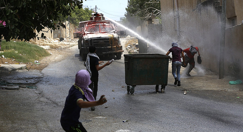 Palestinian protester hurl stones at Israeli Army water canon during clashes which following a protest against Israeli settlements in Qadomem, Kofr Qadom village, near the West Bank city of Nablus, 05 June 2015 (EPA Photo)