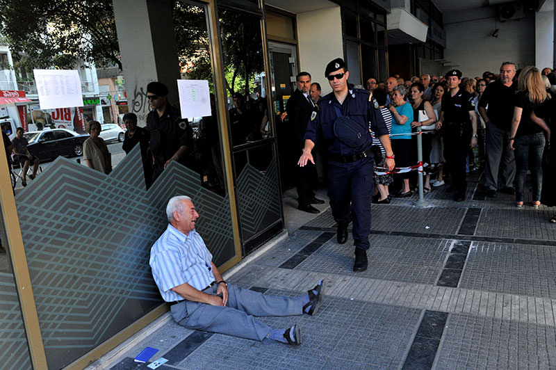 A July 3, 2015 shows Giorgos Chatzifotiadis, sitting on the ground crying outside a national bank branch, as pensioners queue to withdraw their pensions, with a limit of 120 euros, in Thessaloniki (AFP Photo)