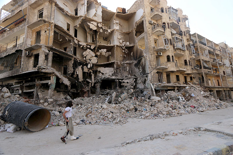 A man walks with the aid of a crutch past damaged buildings in the old city of Aleppo June 27, 2015 (Reuters Photo)