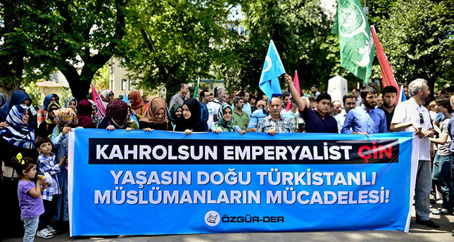Protesters carrying banner which says: Down with Imperialist China, Long live the struggle of East Turkistan Muslims (AA Photo)