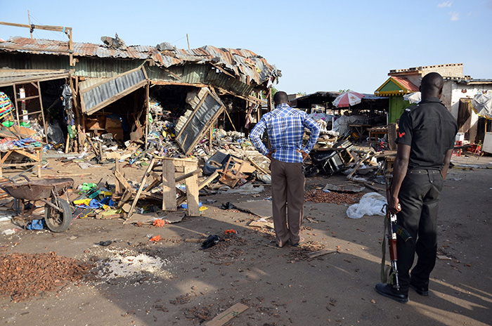 A police officer stands at the scene of a bombing at a bus station in Maiduguri, northeast Nigeria, on June 22, 2015 (AFP Photo)