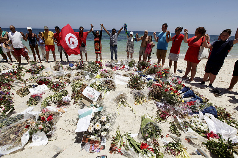 People join hands as they observe a minute's silence in memory of those killed in a recent attack by a gunman, at a beach in Sousse, Tunisia July 3, 2015 (Reuters Photo)