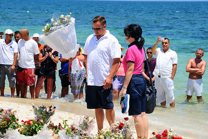 tourists lay flowers to honor the victims of a deadly beach attack a week ago that killed 38 people,in Sousse, Friday, July 3, 2015 (AP Photo)