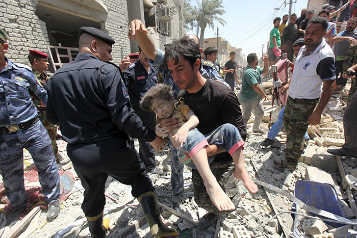 A man carries an injured child found in the rubble after an Iraqi Sukhoi jet accidentally dropped a bomb in Ni'iriya district in Baghdad July 6, 2015.(Reuters Photo)