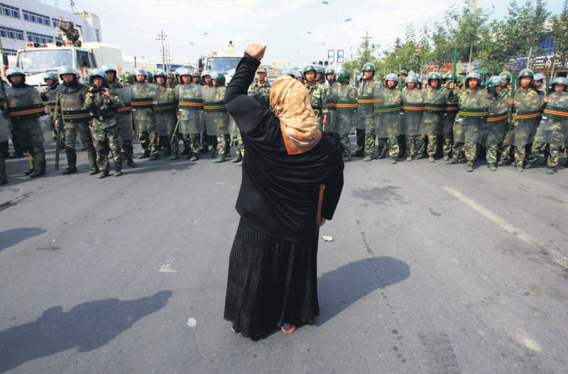 A woman in Xinjiang in 2009 chants slogan against Chinese troops.