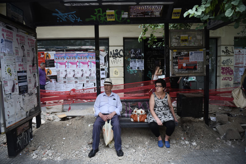 A man and a women sit waiting at a bus stop amid sidewalk construction in Thessaloniki. Capital controls continue as the ECB maintains the liquidity level for Greece.