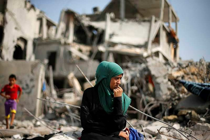 A woman in Gaza sits in front of her demolished house.