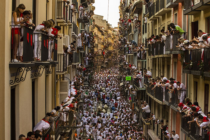 People watch as Jandilla fighting bulls and revelers run during the running of the bulls at the San Fermin festival in Pamplona, Spain, Tuesday, July 7, 2015 (AP Photo)