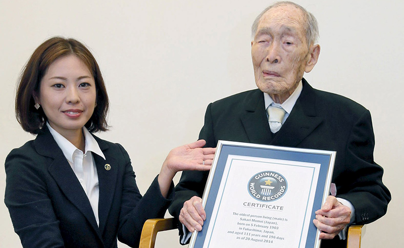 Sakari Momoi (R) receives a Guinness World Records certificate naming him as the world's oldest man at 111 years of age, in Tokyo, in this photo taken by Kyodo August 20, 2014 (Reuters Photo)