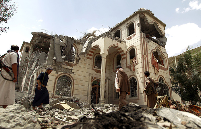 Yemeni armed men walk amidst the debris of a house destroyed in an air-strike by the Saudi-led coalition in the capital Sanaa on July 6, 2015 (AFP Photo)