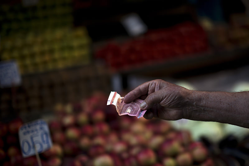A man holds out a ten euro bill as he pays for produce in a fruit market in central Athens, Tuesday, July 7, 2015 (AP Photo)