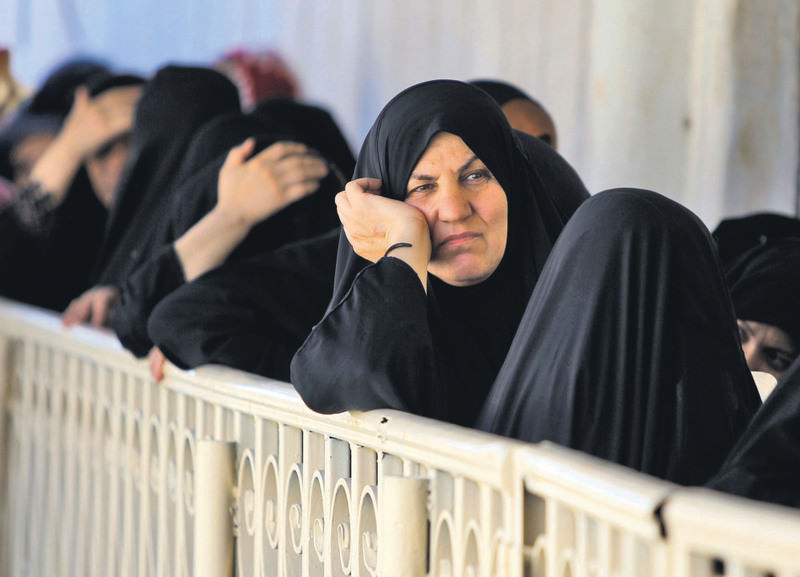 Iraqi refugees who fled Ramadi, after it was seized by the ISIS, await their turn to receive iftar meals during the Islamic holy month of Ramadan.