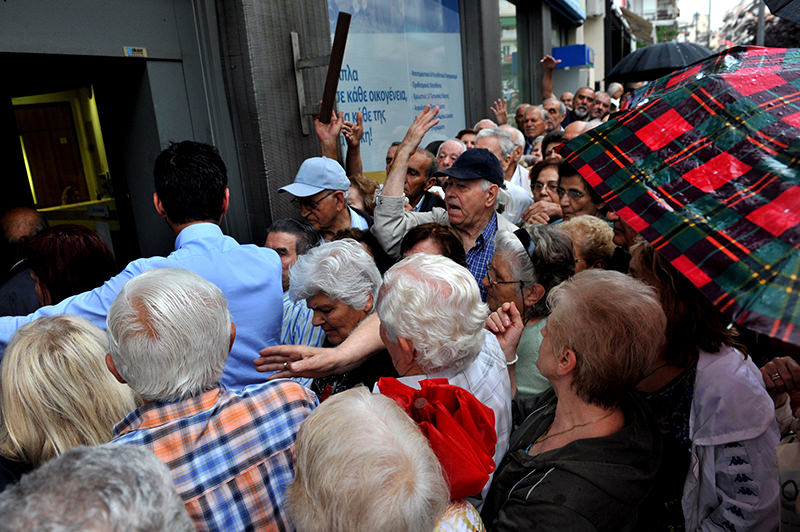 Pensioners without ATM cards queue outside a bank to cash up to 120 euro from their retirement cheques in Thessaloniki on July 1, 2015 (AFP Photo)