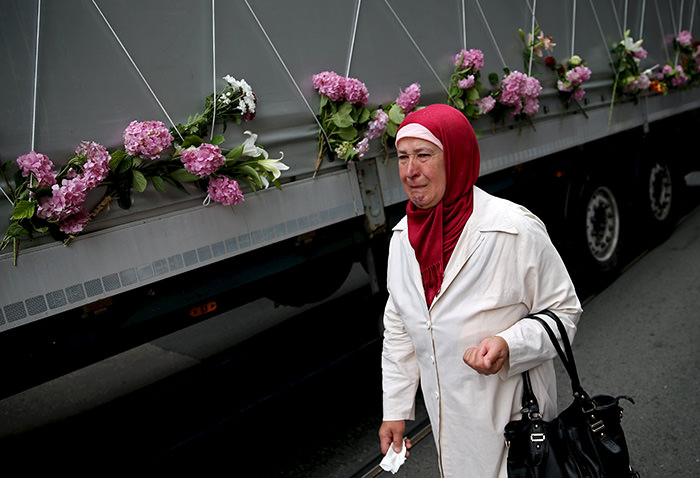 A woman cries near a truck carrying 136 coffins of newly identified victims of the 1995 Srebrenica massacre, in front of the presidential building in Sarajevo July 9, 2015 (AA Photo)