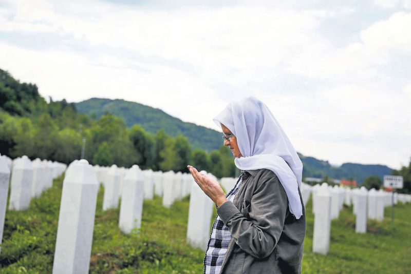 A woman reads prayers in a graveyard where unnamed victims were buried.