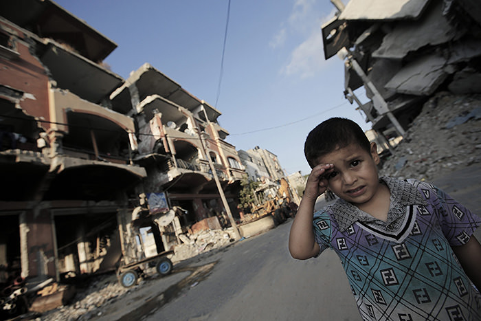 Four-year-old Alaa Al Kafarneh looks on as he plays amid destroyed houses damaged during the 2014 Israel-Gaza conflict, nearly a year later, in Gaza Strip, 03 July 2015 (EPA Photo)