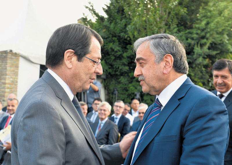 Greek Cypriot President Anastasiades (L) and Turkish Cypriot President Aku0131ncu0131 (R) shake hands at a meeting attended by representatives of the respective chambers of commerce.
