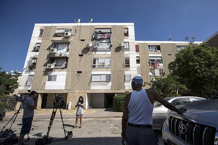 Israeli journalists report outside the apartment building of Ethiopian-Israeli Avraham Mengisto, 28, in the costal city of Ashkelon, Israel, Thursday, July 9, 2015 (AP Photo)