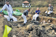 Forensic experts of the International Commission for Missing Persons (ICMP) search for human remains in a mass grave in the village of Kamenica