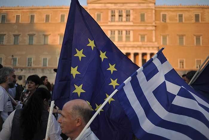 A demonstrator waves Greek and pro Euro flags during a pro euro rally in front of the Greek Parliament in Athens Greece, 09 July 2015 (EPA Photo)