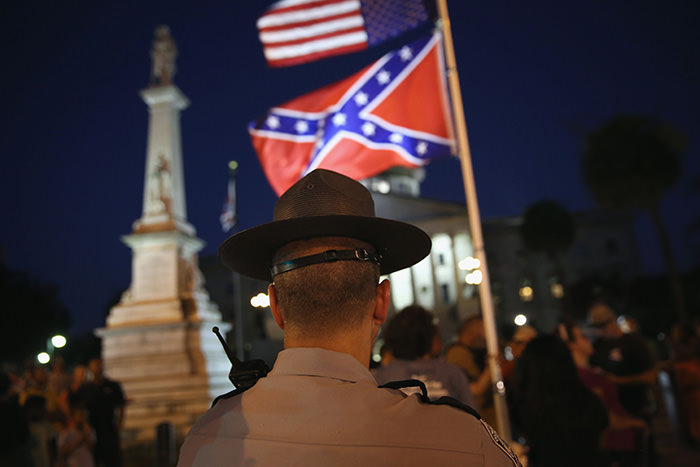 A South Carolina highway patrolman stands guard as the ,Stars and Bars, Confederate flag flies in front of the South Carolina statehouse for its last evening on July 9, 2015 in Columbia, South Carolina (AFP Photo)