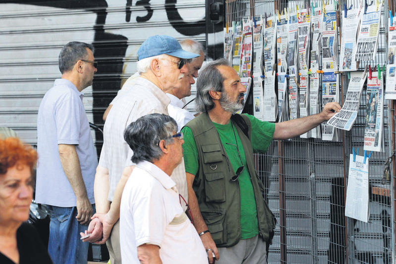 People read the morning newspapers on a kiosk in central Athens on Friday. Prime Minister Alexis Tsipras and Minister of Finance Euclid Tsakalotos briefed in detail the Syriza parliamentary group on the latest developments early the same morning.