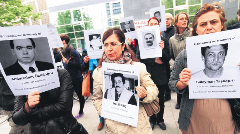 Protesters carrying photos of the NSU's victims outside a Munich courthouse where the gang's sole surviving member, Beate Zschaepe is being tried.
