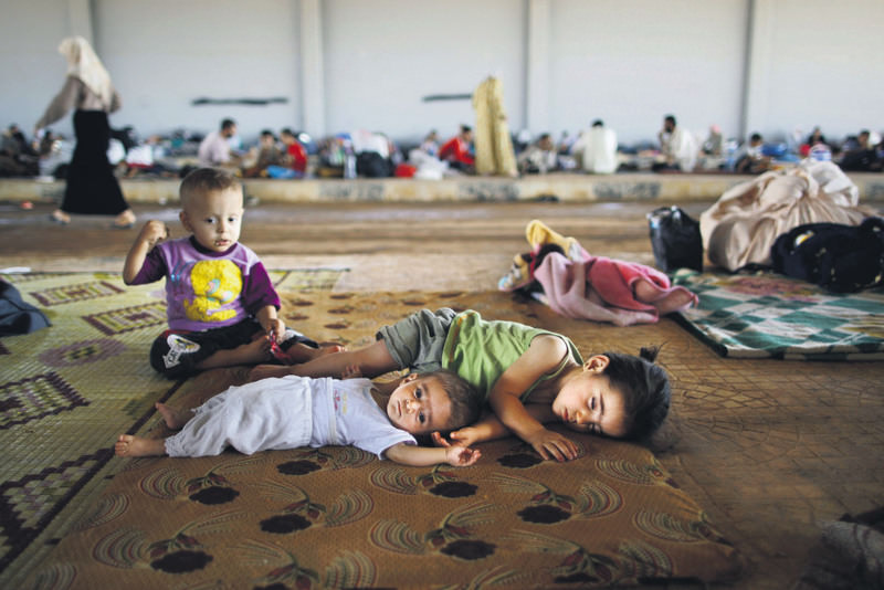 Syrian children who fled from the civil war in Syria lie on the ground while they and others take refuge at the Bab Al-Salameh border crossing near the Syrian town of Azaz in hopes of entering one of the refugee camps in Turkey.