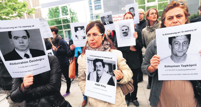Protesters carrying photos of the NSU's victims outside a Munich courthouse where the gang's sole surviving member, Beate Zschaepe is being tried. (AA Photo)