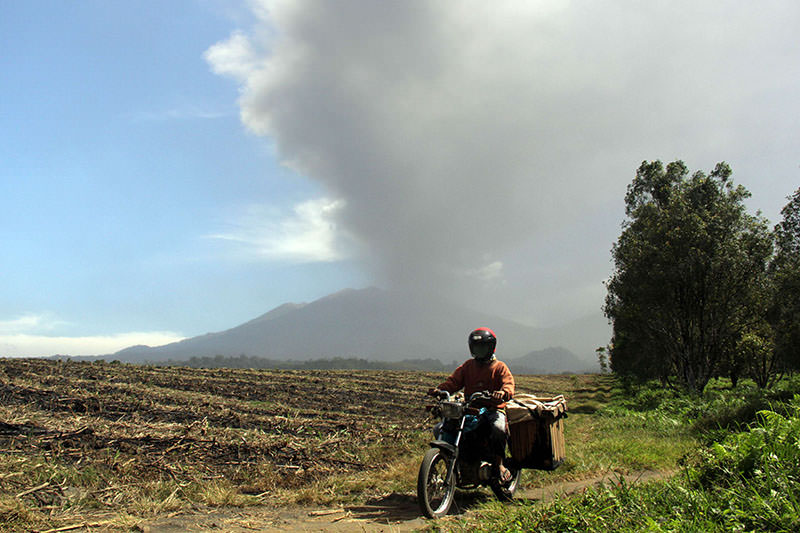 A resident leaves a village in Banyuwangi on July 12, 2015, as the 3,300-metre (10,800-foot) Mount Raung volcano emits a column of ash and steam as seen from Banyuwangi, located in eastern Java island (AFP Photo)