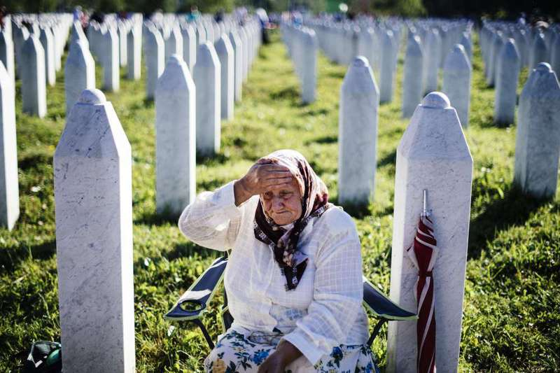 An elderly Bosnian woman mourns at the grave of her relative on July 11, 2015 at the Potocari Memorial Center near the eastern Bosnian town of Srebrenica.