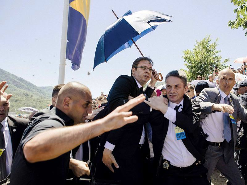 Bodyguards try to protect Serbian Prime Minister Aleksandar Vucic from stones being hurled at him by an angry crowd.