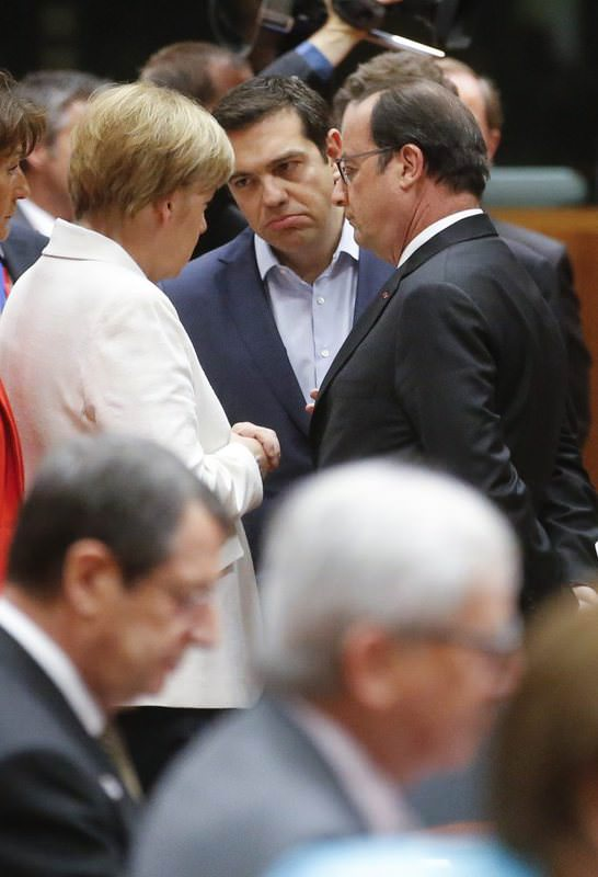 Greek Prime Minister Tsipras (C) talks with German Chancellor Merkel (L) and French President Hollande at the start of eurozone leaders' summit on the Greek crisis at the European Council headquarters in Brussels.