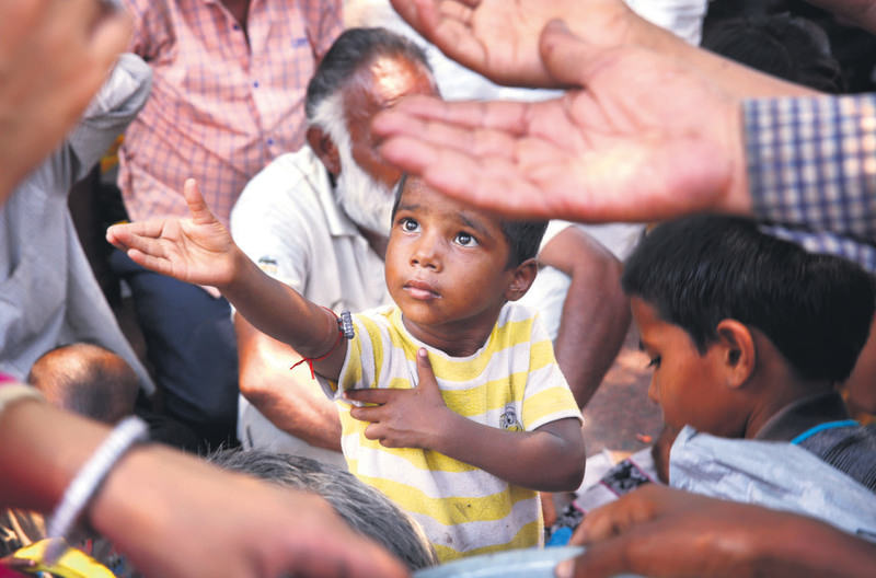 An Indian child stretches arms to receive free food being distributed outside a Hindu temple, in New Delhi, India