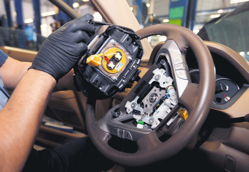 A technician holds a recalled Takata airbag inflator. The yellow circular device is the airbag inflator.