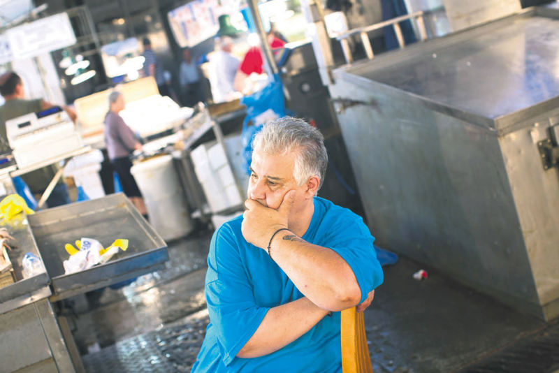A shopkeeper waits for customers at a fish market in central Athens yesterday. Greece's parliament voted on an 85 billion-euro bailout deal meant to confirm harsh reforms asked for by the country's creditors.