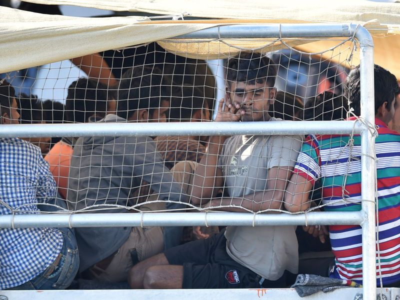 Migrants wait to disembark from the Migrant Offshore Aid Station (MOAS) vessel Phoenix at the harbor of Messina, Sicily on July 15.