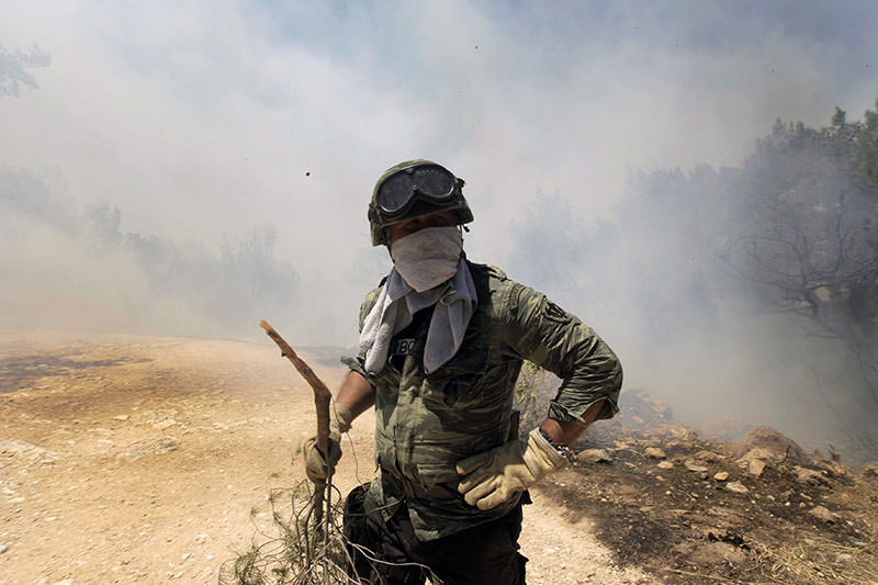 A soldier tries to extinguish a fire in Karea, suburb of Athens, Greece 17 July 2015. Several wildfires have been raging in Greece due to strong winds (EPA Photo)