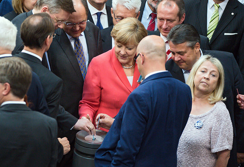 German Chancellor Angela Merkel (C-L) and German Minister for Economy Sigmar Gabriel (R) cast their vote during a special session of the German Bundestag over the proposed bailout package for Greece, in Berlin on 17 July 2015 (EPA Photo)