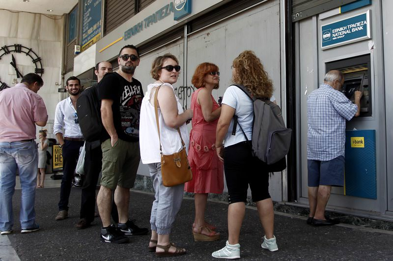 People queue to withdraw money from an ATM outside a branch of Greece's National Bank in Athens, Greece, 06 July 2015 (EPA Photo)